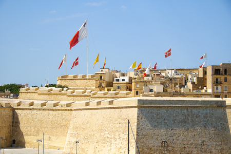 flagging: The view of Post of Castile with the flags flaping over the fortress walls for a holiday. Malta