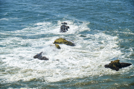 vicinity: Rocks and waves of surf in the ocean near Farol De Nazare coast, in vicinity of portuguese town Nazare, Portugal