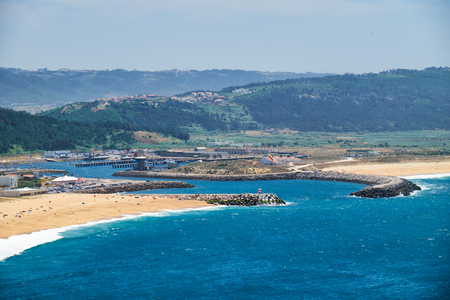 Birds-eye view on Nazare beach riviera on the coast of Atlantic ocean with Nazare town. Portugal