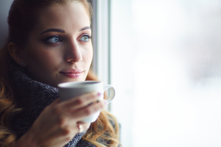 mujer rubia desnuda: Young pretty woman in wool sweater with white coffee cup in hands near window