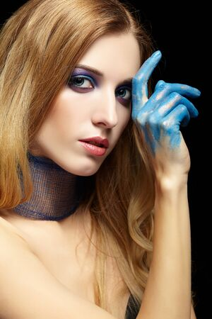 Young blonde woman with long hair and hands painted in blue paint