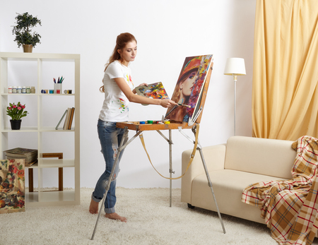 Painter woman with wooden sketchbook and painting female portrait