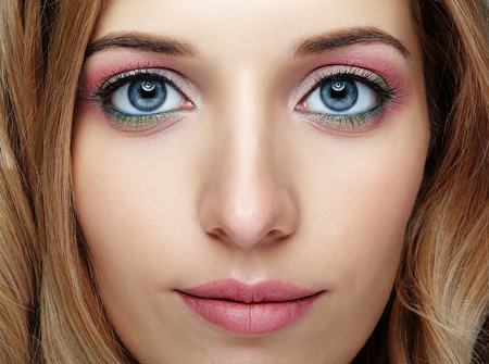 Closeup shot of female face with pink and green blue eyes makeup Stock Photo
