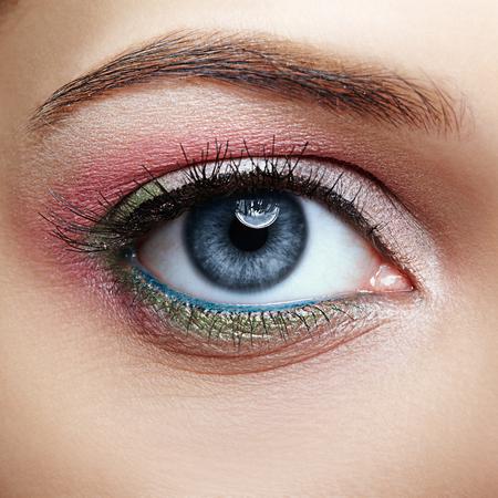 Nahaufnahmemakrobild des menschlichen weiblichen Auges mit rosafarbenem und grünem Make-up