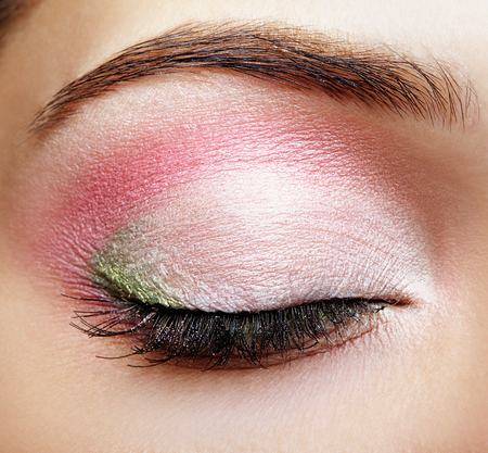 Closeup macro shot of closed human female eye with pink and green makeup photo