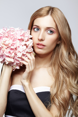 Closeup portrait of young beauty woman in black and white dress and blond hair with hydrangea bouquet flowers in hands photo