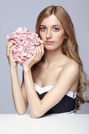 Portrait of young beauty woman in black and white dress and blond hair sitting at the white table with hydrangea bouquet flowers in hands photo