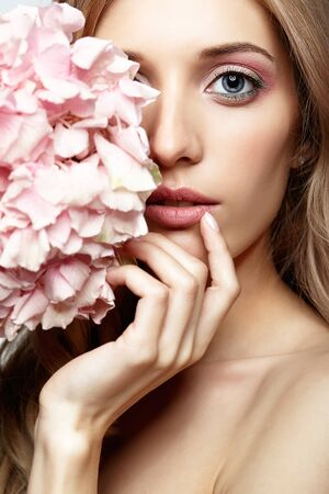 Closeup portrait of young beauty female face with blond hair and hydrangea bouquet flowers near face photo