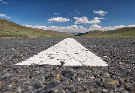 street shot: Wide-angle shot of empty road markings on asphalt in Mongolia between mongolian towns Tsagaannuur and Bayan-Olgii under blue sky