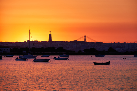 Sunset view of the river Tejo, 25th of April Bridge and statue of  Christ the King in Lisbon, Portugal Editorial