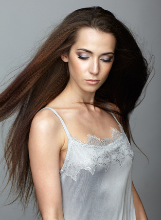 peignoir: Beauty portrait of young woman. Brunette girl with long disheveled flying hair and day female makeup on gray background.