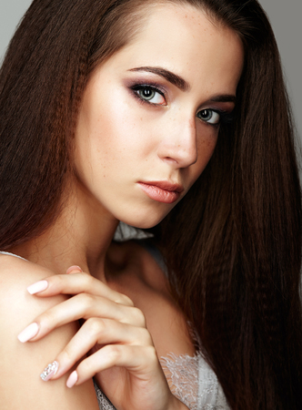 Closeup beauty portrait of young woman. Brunette girl with long hair and day female makeup. Stock Photo