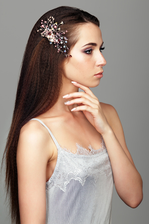 Beauty portrait of young woman. Brunette girl with brooch in long hair and day female makeup on gray background.