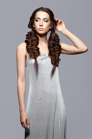 Beauty portrait of young woman in nightie. Brunette girl with long hair plaits and day female makeup on gray background.