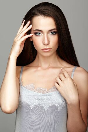 nighty: Beauty portrait of young woman. Brunette girl with long hair and day female makeup on gray background.