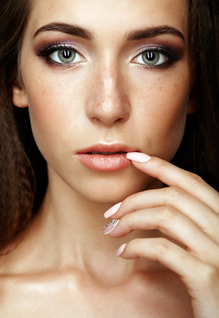 nighty: Beauty portrait of young woman touching face with fingers. Brunette girl with long hair and day female makeup on gray background.