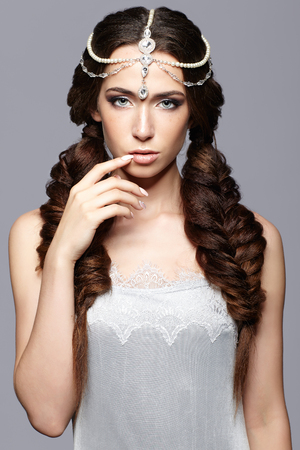 Beauty portrait of young woman with diadem. Brunette girl with long hair braids and day female makeup on gray background.