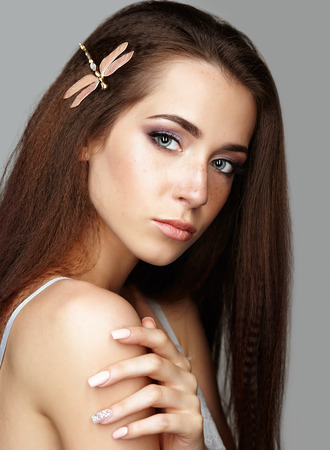 nighty: Beauty portrait of young woman. Brunette girl with dragonfly brooch in long hair and day female makeup on gray background. Stock Photo