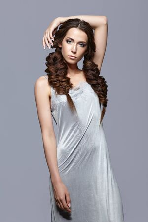 nighty: Beauty portrait of young woman in nightie. Brunette girl with long hair plaits and day female makeup on gray background.