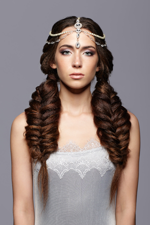 nighty: Beauty portrait of young woman with diadem. Brunette girl with long hair braids and day female makeup on gray background.