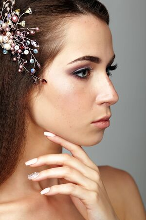 Beauty portrait of young woman touching face with fingers. Brunette girl with brooch in long hair and day female makeup on gray background.