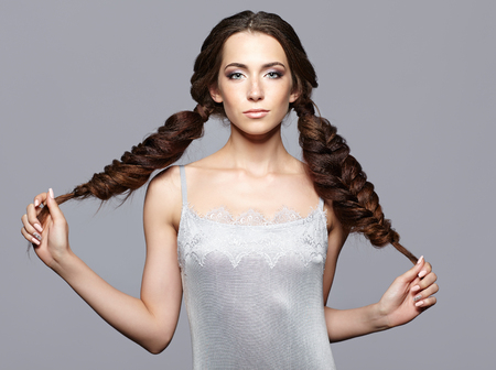 nighty: Beauty portrait of young woman. Brunette girl holding long hair braids on gray background.