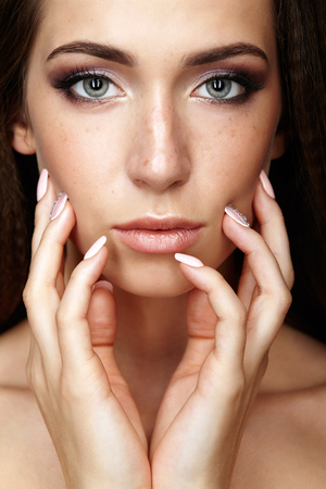Beauty portrait of young woman touching face with fingers.  Brunette girl with long hair and day female makeup. Stock Photo