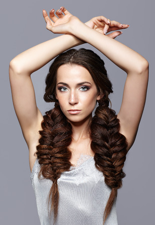 nighty: Beauty portrait of young woman with hands up. Brunette girl with long hair braides, and day female makeup on gray background.
