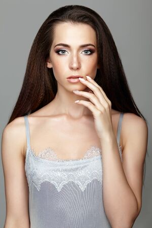 Beauty portrait of young woman touching face with fingers. Brunette girl with long hair and day female makeup on gray background.