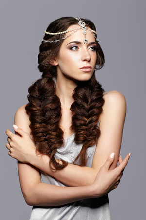 nighty: Beauty portrait of young woman with diadem. Brunette girl with long hair plaits and day female makeup on gray background.