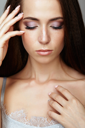 nighty: Beauty portrait of young woman touching face with fingers. Brunette girl with long hair and day female makeup.