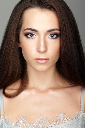 Beauty portrait of young woman. Brunette girl with long hair and day female makeup on gray background.
