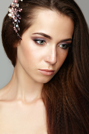 nighty: Beauty portrait of young woman. Brunette girl with brooch in long hair and day female makeup on gray background.