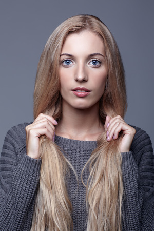 Portrait of young woman in gray woolen sweater. Beautiful girl posing on grey studio background. Female holding bunches of blond hair in hands.