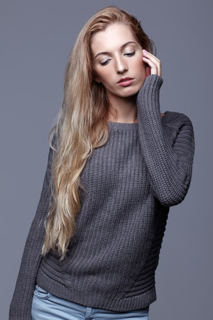 Portrait of young woman in gray woolen sweater and jeans. Beautiful girl posing on grey studio background. Female with blonde hair and day beauty makeup. photo