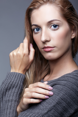 Portrait of young woman in gray woolen sweater. Beautiful girl posing on grey studio background. Female with blonde hair and day beauty makeup. photo