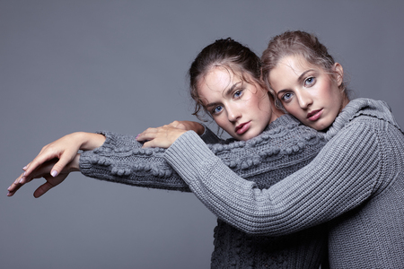Two young women in gray sweaters on grey studio background. Beautiful girls stretching hands forward in embrace. Female friendship concept. photo