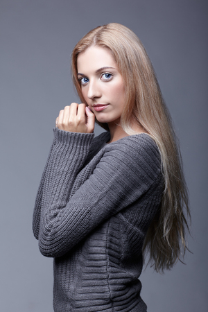 Portrait of young romantic woman in gray woolen sweater. Beautiful girl posing on grey studio background. Female with blonde hair and day beauty makeup touching face. photo