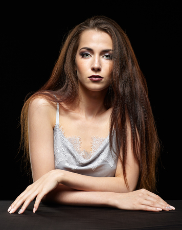 Beauty portrait of young woman sit at the black table. Brunette girl with long hair and evening female makeup on dark background.