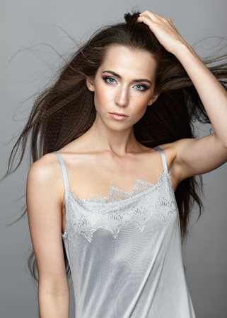 nighty: Beauty portrait of young woman. Brunette girl with long disheveled flying hair and day female makeup on gray background.