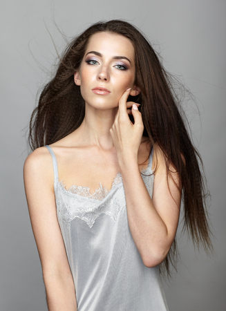 Beauty portrait of young woman. Brunette girl with long disheveled flying hair and day female makeup on gray background.