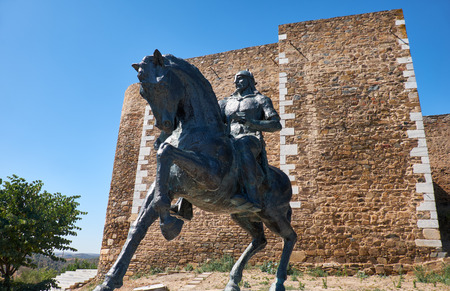 An equestrian statue of Ibn Qasi, the proclaimed political and spiritual leader of the taifa kingdom of Mertola, with the keep tower of Mertola Castle on the background. Mertola. Portugal Editorial