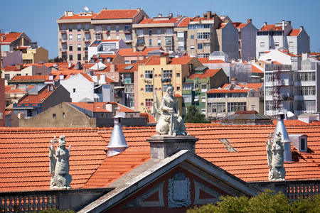 The view of Alfama houses with tile roof and pediment  decorated with sculptures on the foreground as seen from the roof terrace of National Pantheon. Lisbon. Portugal