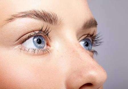 女性の顔のクローズ アップ マクロ肖像画。人間の女性は、美容の日のメイクと青い目を開きます。完璧な肌とそばかすの女の子。
