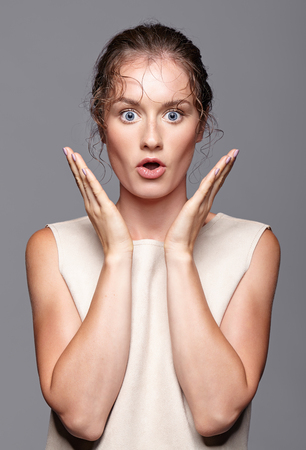 Amazed young woman with hands near face and mouth open. Shocked girl with bulging eyes. Surprised female screaming with expressive facial expressions Stock Photo