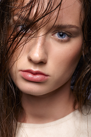 Beauty portrait of young woman. Brunette girl with bright blue eyes and day female makeup on gray background.