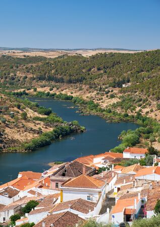 View of Guadiana river bend and residential houses of Mertola city on the riverside as seen from the Castle hill. Mertola. Baixo Alentejo. Portugal Stock Photo