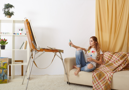 Painter woman on sofa with wooden sketchbook and painting Stock Photo