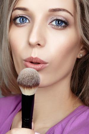 Blonde beauty female stylist - visagist blows on makeup brush