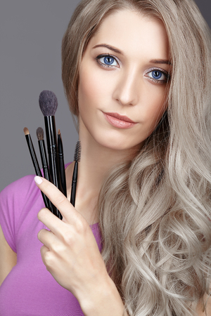 Blonde beauty female stylist - visagist with makeup brushes in hands